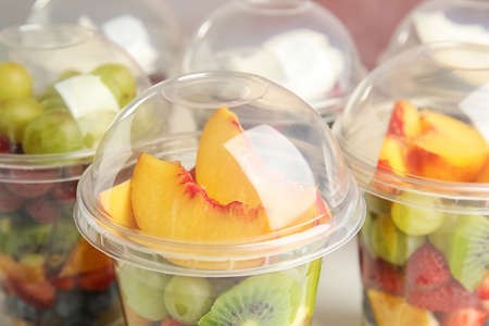 Fresh tasty fruit salad in plastic cups, closeup 免版税图像