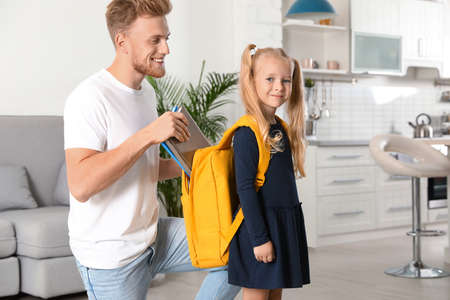 Happy father putting textbooks into little child's school bag at home