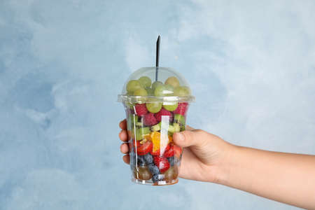 Woman holding plastic cup with fresh tasty fruit salad against light blue background, closeup