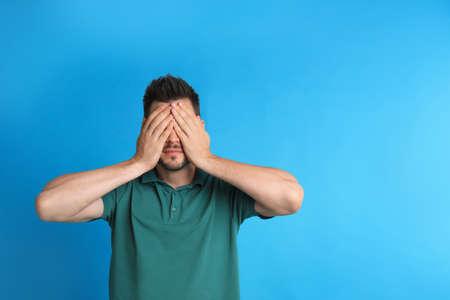 파란색 배경에 눈이 멀면서 눈을 가린 남자