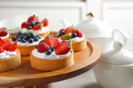 Cake stand with different berry tarts on table. Delicious pastries