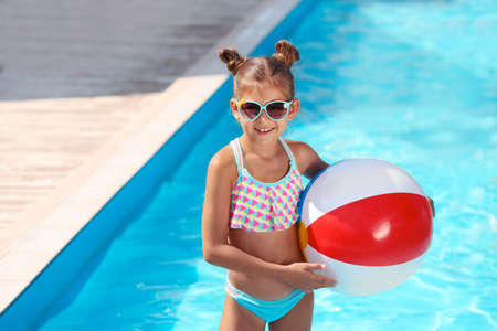 Cute little girl with inflatable ball in swimming pool Foto de archivo