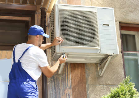 Professional technician maintaining modern air conditioner outdoors Imagens