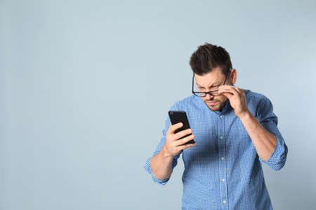 Man with vision problems using smartphone on grey background, space for text