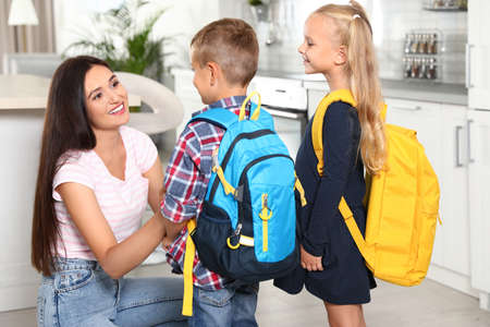 Heureuse mère et petits enfants avec des sacs d'école dans la cuisine