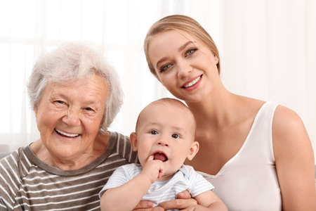 Happy young woman with her child and grandmother at home