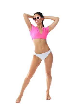 Mooie jonge vrouw in stijlvolle bikini met zonnebril op witte achtergrond