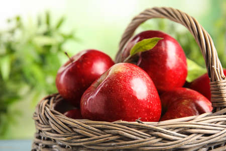 Wicker basket with ripe juicy red apples against blurred background, closeup