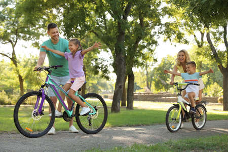 Genitori felici che insegnano ai loro figli ad andare in bicicletta nel parco
