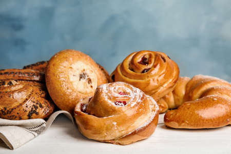 Different delicious fresh pastries on white wooden table