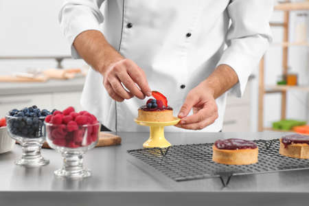 Male pastry chef preparing dessert at table in kitchen, closeup