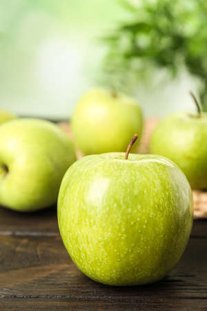 Fresh ripe green apple on dark wooden table against blurred background, closeup view. Space for text