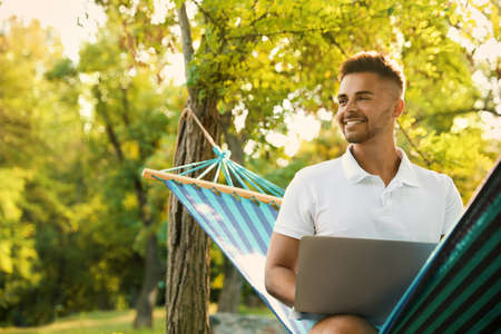 Junger Mann mit Laptop in bequemer Hängematte im grünen Garten