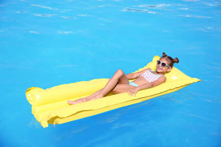 Cute little girl on inflatable mattress in swimming pool