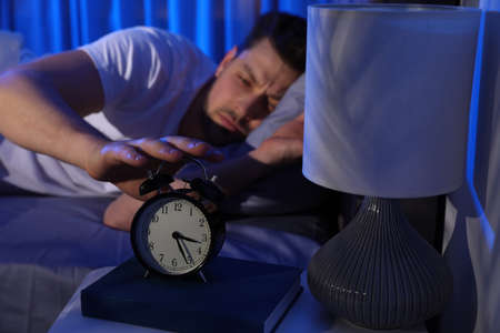 Sleepy man turning off alarm clock in dark room. Bedtime