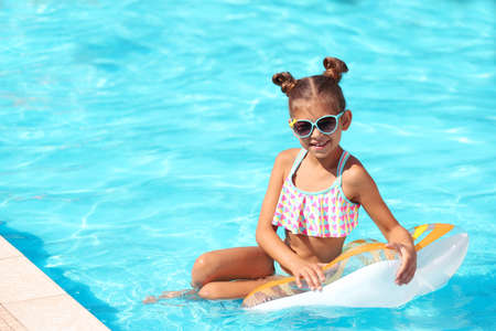 Cute little girl with inflatable ring in swimming pool