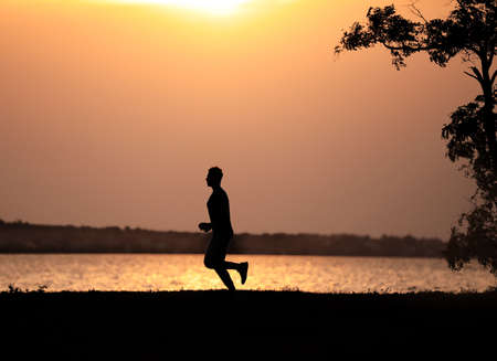 Young man running near river at sunset