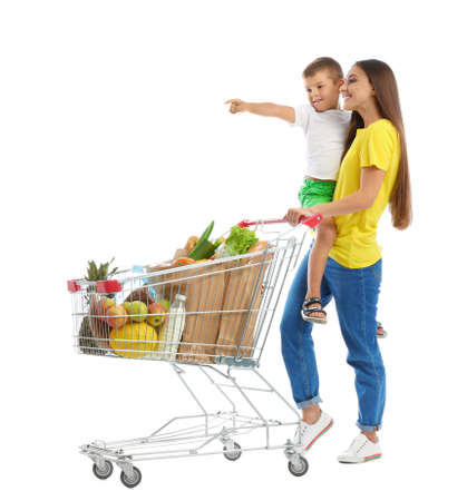 Mother and son with full shopping cart on white background