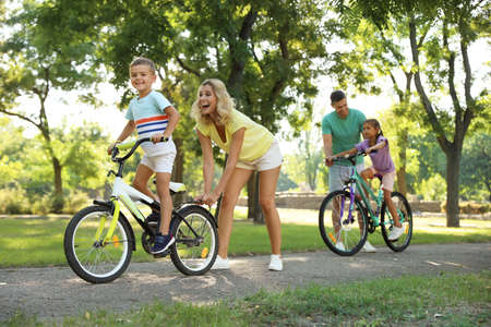 Happy parents teaching their children to ride bicycle in park