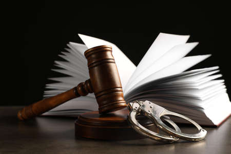 Judge's gavel, handcuffs and book on grey table against black background. Criminal law concept