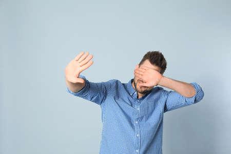 Handsome man being blinded on grey background