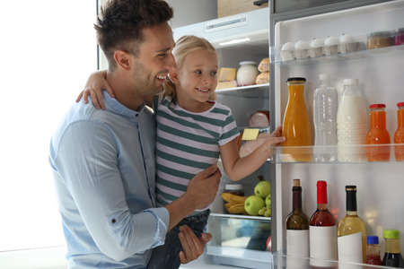 Father and daughter taking bottle with juice out of refrigerator in kitchen