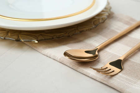 Beautiful table setting with gold cutlery on grey background Stock Photo - 130129879