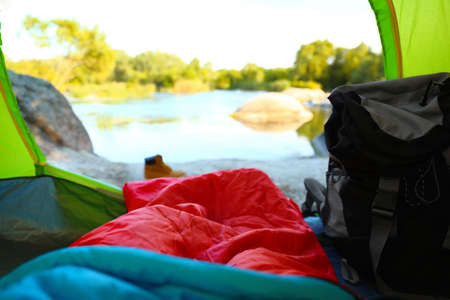 Camping tent with sleeping bag near lake, view from inside