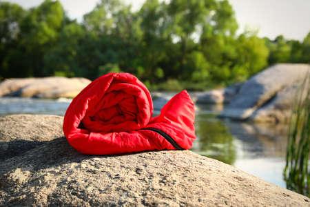 Rolled sleeping bag near lake on sunny day