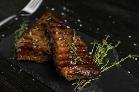 Board with grilled meat on wooden table Stock Photo