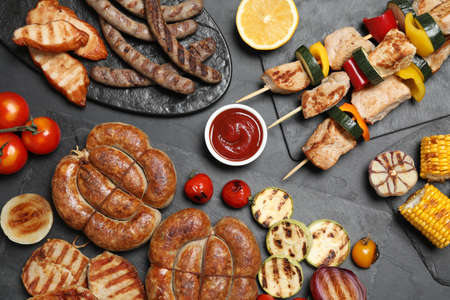 Flat lay composition with barbecued meat and vegetables on grey table