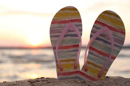 Stylish flip flops on sand near sea, closeup. Beach accessories