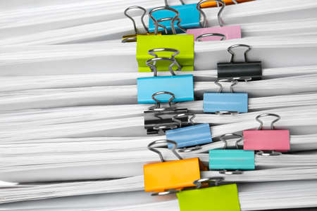 Stack of documents with binder clips as background, closeup view