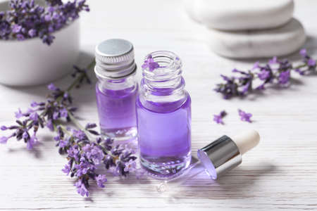 Glass bottles of natural cosmetic oil and lavender flowers on white wooden table
