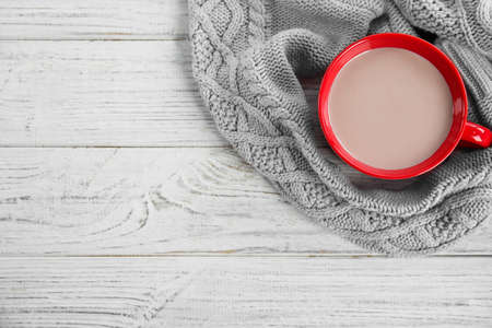 Cup of hot cocoa and knitted sweater on white wooden table, top view with space for text. Winter drink
