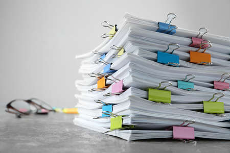 Stack of documents with binder clips on grey stone table, closeup view. Space for text Stock Photo - 130132270