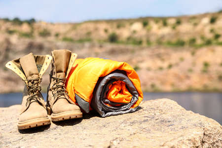 Sleeping bag and boots on cliff near lake. Space for text