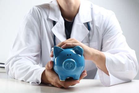 Doctor with piggybank at white table indoors, closeup. Medical insurance concept Stock Photo - 130132430