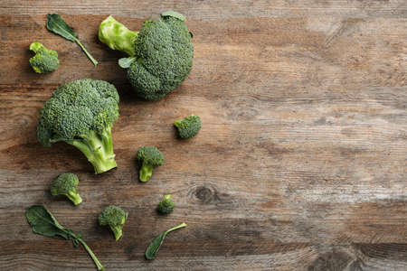 Fresh raw broccoli florets on wooden table, flat lay with space for text