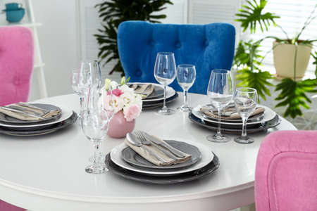 Beautiful table setting in modern dining room interior