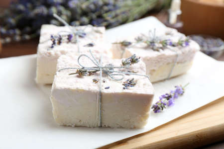 Hand made soap bars with lavender flowers on white paper, closeup