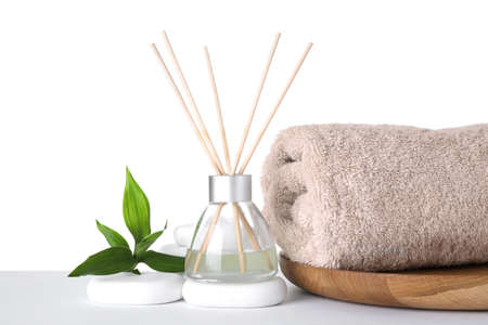 Composition with towel, air freshener and spa stones isolated on white Фото со стока