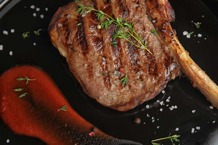 Delicious grilled meat steak with garnish on plate, closeup