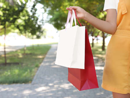 Young woman with shopping bags in sunny park, closeup