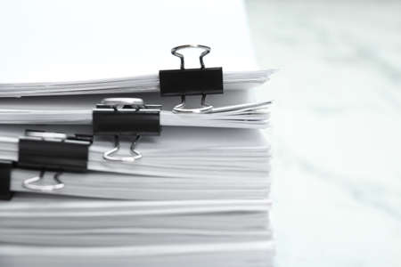 Stack of documents with binder clips on marble table, closeup Stock Photo