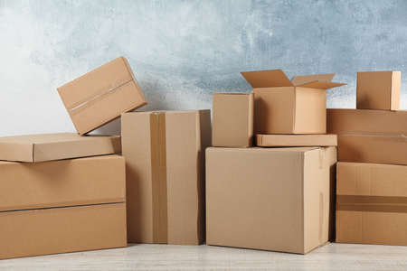 Pile of cardboard boxes near color wall indoors Stock Photo - 130132652