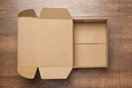 Open cardboard box on wooden background, top view
