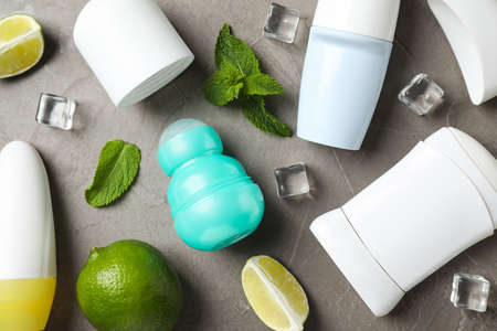 Flat lay composition with female roll-on deodorants on grey table