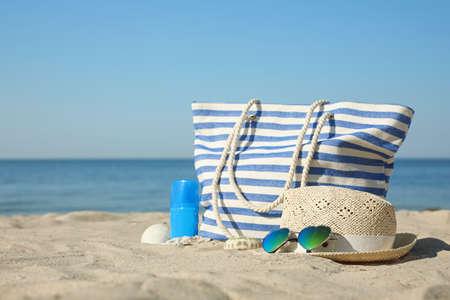Stylish beach accessories on sandy sea shore Imagens
