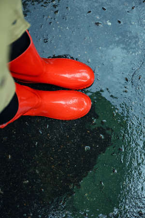 Woman wearing red rubber boots on rainy day, above view